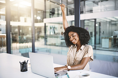 Buy stock photo Shot of a happy young businesswoman celebrating at her desk in a modern office