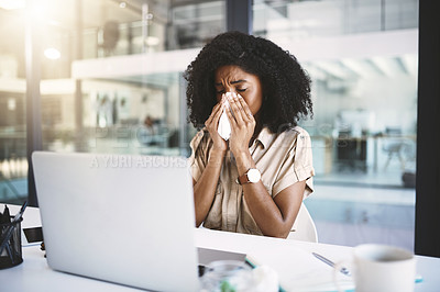 Buy stock photo Shot of a young businesswoman blowing her nose with a tissue while working in a modern office