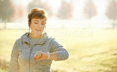 Buy stock photo Cropped shot of an attractive mature sportswoman checking on her time during an early morning workout in the park