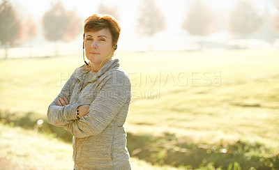 Buy stock photo Cropped portrait of an attractive mature sportswoman standing with her arms folded in the park during an early morning workout