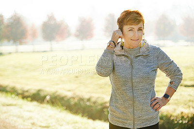 Buy stock photo Cropped portrait of an attractive mature sportswoman standing with her hand on her hip in the park during an early morning workout
