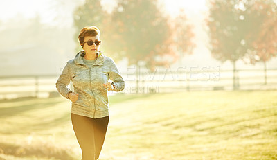Buy stock photo Cropped shot of an attractive mature sportswoman out for an early morning run in the park