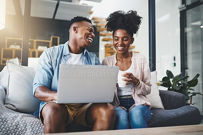 Buy stock photo Shot of a happy young couple using a laptop together on the sofa at home