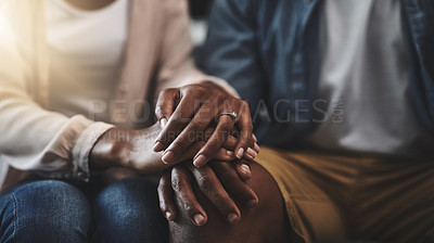 Buy stock photo Cropped shot of a man and woman sitting on a sofa and holding hands