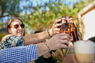 Buy stock photo Shot of a group of young friends toasting with drinks at an outdoor get together