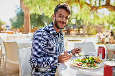 Buy stock photo Shot of a young man having lunch in a garden