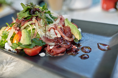Buy stock photo Shot of a plate of healthy salad on a table outdoors