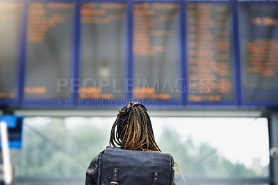 Buy stock photo Rearview shot of a young woman reading an information display in a transport facility