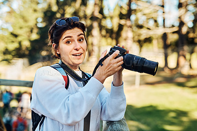Buy stock photo Cropped portrait of an attractive young female birdwatcher snapping pictures while exploring outdoors