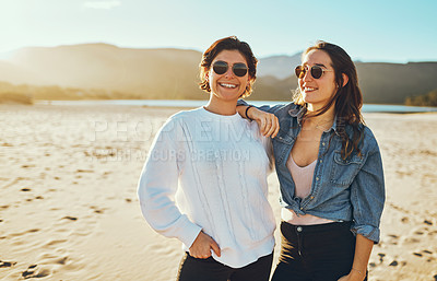 Buy stock photo Cropped shot of two attractive young woman enjoying their day out on the beach