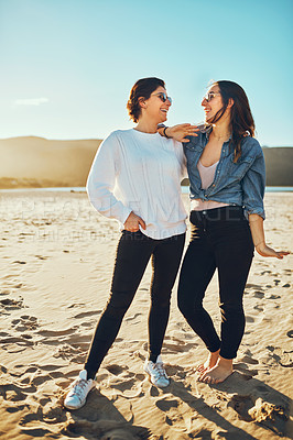 Buy stock photo Full length shot of two attractive young woman enjoying their day out on the beach