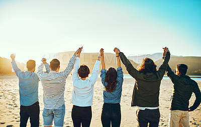 Buy stock photo Rearview shot of a group of unrecognizable young friends standing with their arms raised on the beach