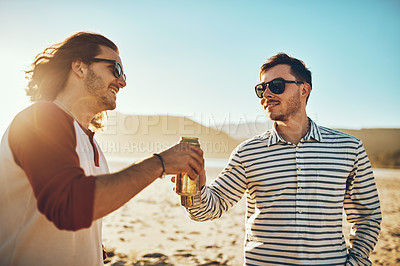 Buy stock photo Cropped shot of two handsome young male friends cheersing with beers on the beach