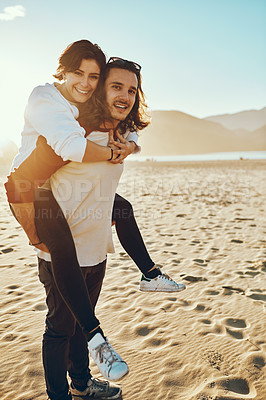 Buy stock photo Full length portrait of a handsome young man piggybacking his girlfriend while enjoying their day at the beach