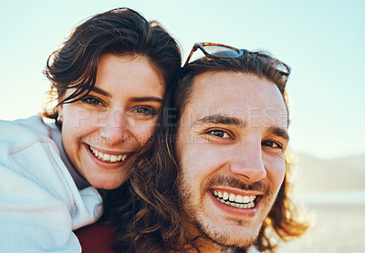 Buy stock photo Cropped portrait of a handsome young man piggybacking his girlfriend while enjoying their day at the beach