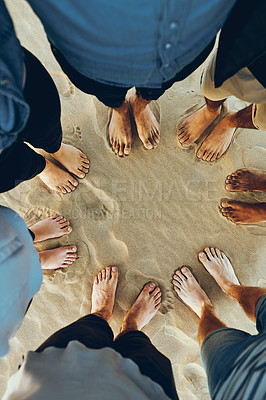 Buy stock photo High angle shot of an unrecognizable group of young friends standing barefoot in a huddle with their feet in the sand