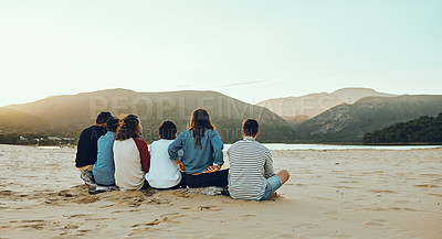 Buy stock photo Rearview shot of an unrecognizable group of young friends sitting on the sand at the beach