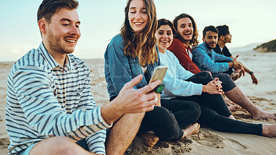 Buy stock photo Cropped shot of a group of young friends sitting on the sand at the beach