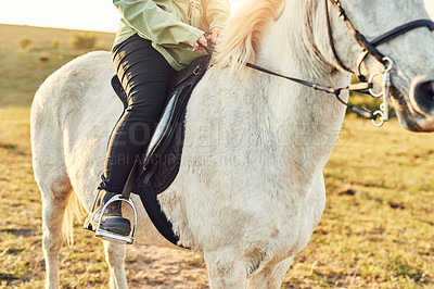 Buy stock photo Cropped shot of a woman riding a horse on a farm