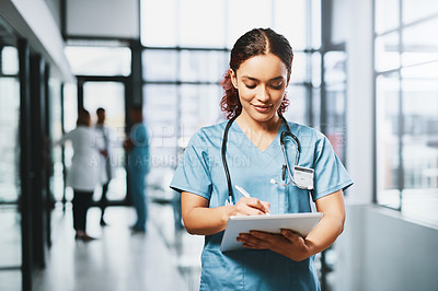 Buy stock photo Shot of a young nurse using a digital tablet in a hospital