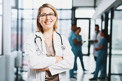Buy stock photo Portrait of a young doctor standing with her arms crossed in a hospital