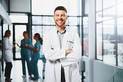Buy stock photo Portrait of a mature doctor standing with his arms crossed in a hospital
