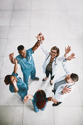 Buy stock photo High angle shot of a group of medical practitioners raising their hands together in unity