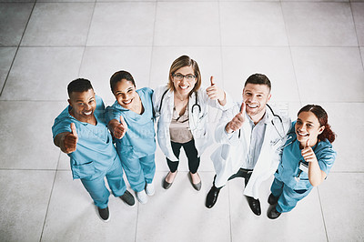 Buy stock photo Portrait of a group of medical practitioners showing thumbs up in a hospital