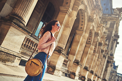 Buy stock photo Low angle shot of an attractive young woman exploring the city of Paris in France