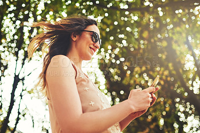 Buy stock photo Low angle shot of an attractive young woman sending text messages while exploring the city of Paris in France
