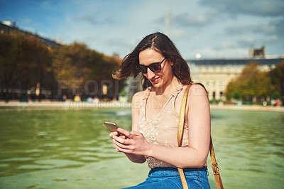 Buy stock photo Cropped shot of an attractive young woman sending text messages while exploring the city of Paris in France