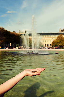 Buy stock photo Cropped shot of an unrecognizable young woman dropping coins into a pond while exploring the city of Paris in France