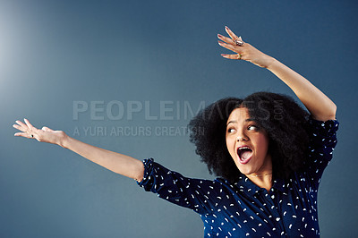 Buy stock photo Studio shot of a young woman gesturing towards copy space against a blue background