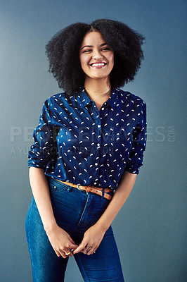 Buy stock photo Studio portrait of an attractive young woman against a blue background