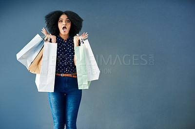 Buy stock photo Studio portrait of a young woman carrying shopping bags and looking surprised against a blue background