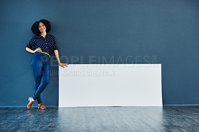 Buy stock photo Studio shot of a young woman leaning against a blank placard against a blue background