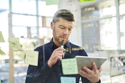 Buy stock photo Shot of a mature businessman using a digital tablet while brainstorming on a glass wall in an office