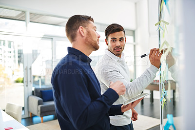 Buy stock photo Shot of two businessmen brainstorming on a glass wall in an office