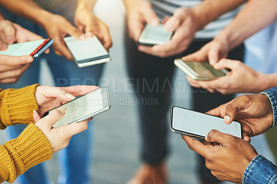 Buy stock photo Cropped shot of a group of unrecognizable young businesspeople using their cellphones while standing in a circle in their office