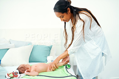 Buy stock photo Shot of a mother applying body lotion on her baby boy after giving him a bath at home