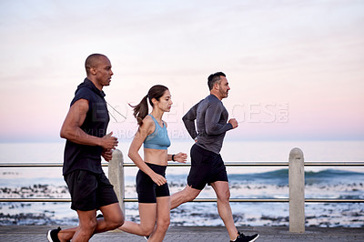 Buy stock photo Shot of a fitness group exercising together outdoors