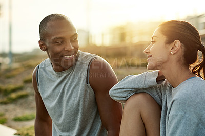 Buy stock photo Shot of a sporty young man and woman taking a break while exercising outdoors
