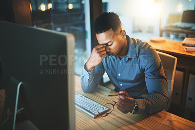 Buy stock photo Cropped shot of a handsome young businessman looking stressed while working late at night in a modern office