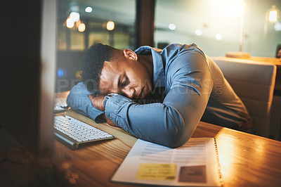 Buy stock photo Cropped shot of a handsome young businessman sleeping at his desk while working late at night in a modern office