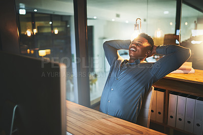 Buy stock photo Cropped shot of a handsome young businessman looking relaxed while working late at night in a modern office