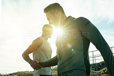Buy stock photo Shot of two sporty men shaking hands while exercising outdoors