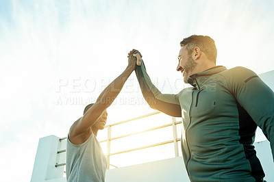 Buy stock photo Low angle shot of two sporty men giving each other a high five while exercising outdoors