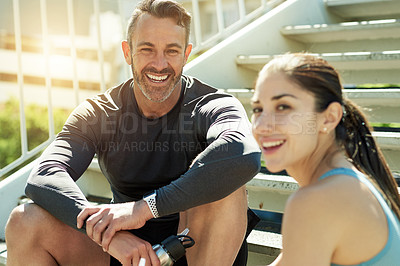 Buy stock photo Portrait of a sporty couple taking a break while exercising outdoors