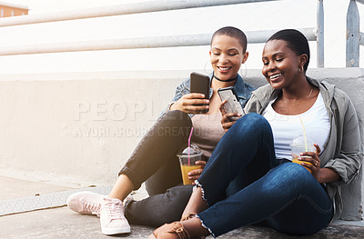 Buy stock photo Shot of two young women in the city sitting down while laughing and holding their drinks reading through text messages