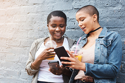 Buy stock photo Shot of two young women standing beside a building smiling and reading through text messages while holding their cool drinks
